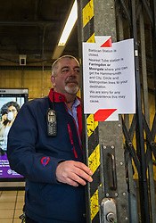 © Licensed to London News Pictures. 19/03/2020. London, UK. A member of station staff at Barbican tube station near St Bartholomew's Hospital in London which is seen closed this morning. Transport for London (TfL) are closing a number of underground stations from today, as partial closure of the tube and rail network begins in response to the growing coronavirus outbreak in the captial. Photo credit: Vickie Flores/LNP
