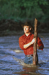 good looking cowboy in a river fixing a fence