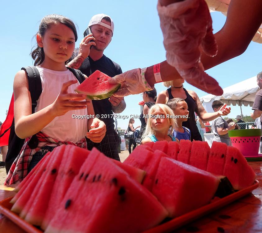 新华社照片,洛杉矶,2017年7月30日<br />     (国际)(1)第五十五届加州西瓜节<br />     7月29日,民众品尝鲜甜西瓜。<br />     在美国洛杉矶,大批民众出席了&quot;第五十五届加州西瓜节&quot;。<br />     新华社发(赵汉荣摄)<br /> People line for watermelon at the 55th Annual California Watermelon Festival in Los Angeles, the United States, Saturday, July 29, 2017. (Xinhua/Zhao Hanrong)