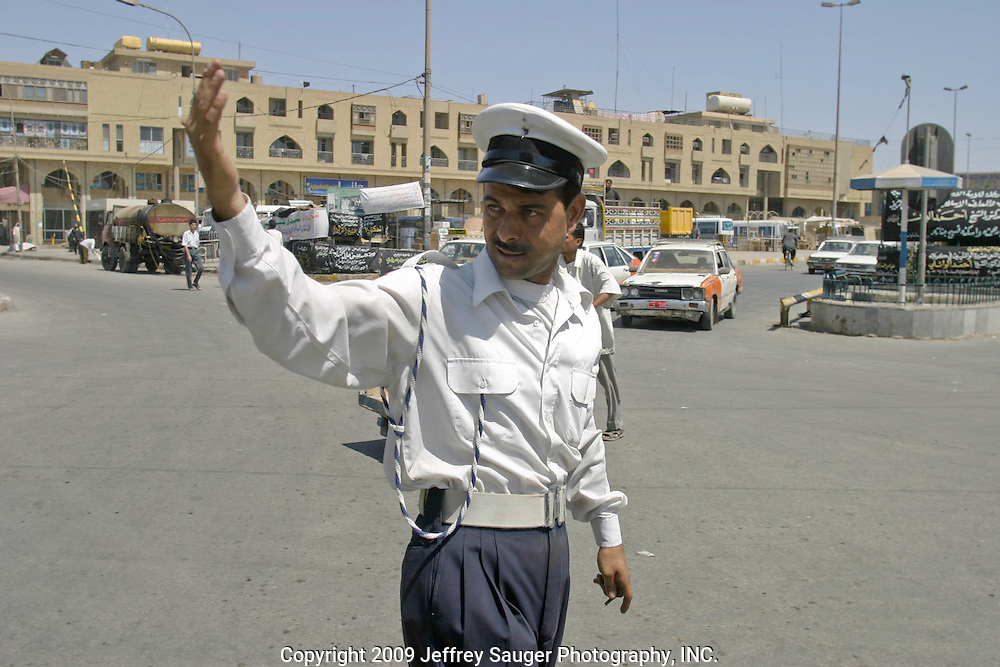 An Iraqi traffic officer directs traffic in Karbala, Iraq, Monday, July 21, 2003.They stopped working one week before the war and returned to work after April 9, the day most recognize as the day Saddam Hussein's government fell.Things are returning to normal but, it will take time for security police to be trained and assigned to their duty.