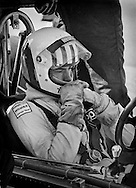 Welsh F1 driver Tom Pryce uses a break in practice for the 1975 United States Grand Prix to mentally &ldquo;search for time&rdquo; in the UOP Shadow. <br /> <br /> Pryce was just beginning to position himself for future stardom by the end of the season. <br /> <br /> He had used his 1974 Monaco Formula 3 victory as a tried-and-true stepping-stone into Formula 1, and by the summer of 1975, he had already captured the pole for the British Grand Prix and began scoring points. That year he also won the non-points Formula 1 Race of Champions. <br /> <br /> He remained at Shadow in 1976 and into 1977. Tragically, he was killed during the South African Grand Prix when a corner marshall suddenly ran into his path while trying to aid another car. Both died instantly. <br /> <br /> Had he survived, Pryce would have challenged the best for championships.