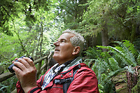 Senior man in forest looking up holding binoculars
