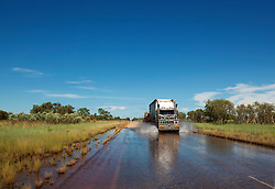 A roadtrain passes through water on the road to Fitzroy Crossing in the wet season.