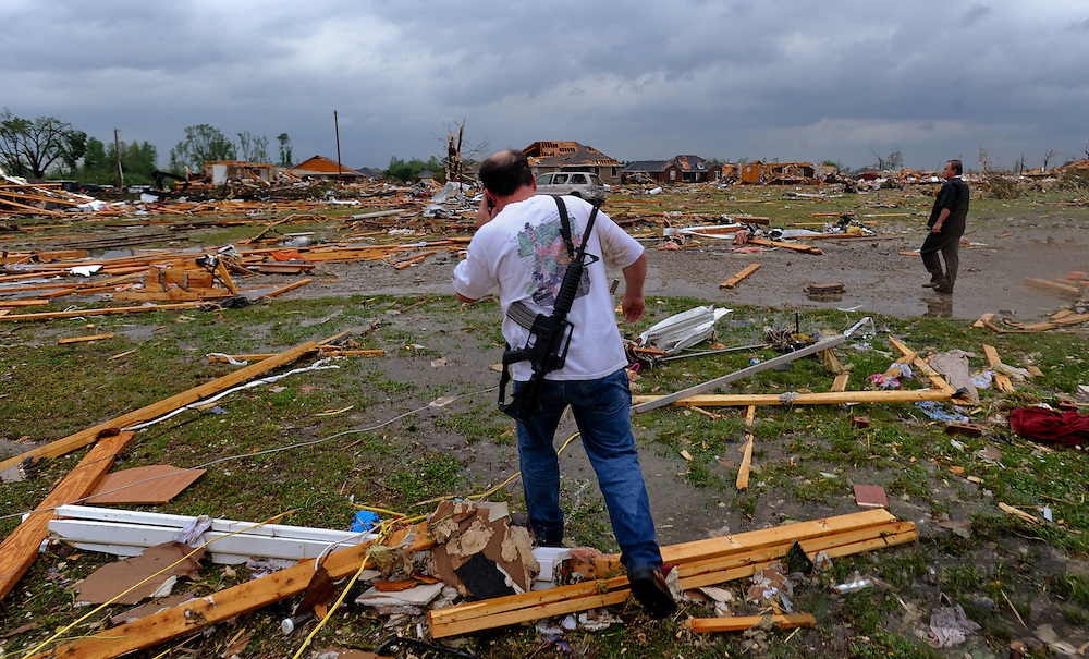 Photo by Gary Cosby Jr.  Homes in the McCulley Mill Rd. area are completely destroyed following a large tornado that cut a path through Lawrence, Morgan and Limestone Counties.  Kevin Harrison carries a rifle on his back as he searches for neighbors in his destroyed neighborhood.