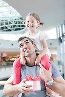 Young daughter sits on fathers shoulders