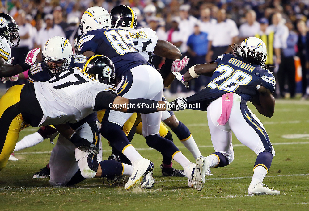 San Diego Chargers running back Melvin Gordon (28) has his jersey pulled by Pittsburgh Steelers defensive end Cameron Heyward (97) as he runs the ball during the 2015 NFL week 5 regular season football game against the Pittsburgh Steelers on Monday, Oct. 12, 2015 in San Diego. The Steelers won the game 24-20. (©Paul Anthony Spinelli)