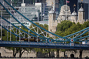 A cityscape of the City of London in the background with the northern steel suspension chains and hangers of Tower Bridge and the Norman-era Tower of London flying the British Union Jack flag, on 14th September 2017, in London, England.