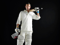 Cricket player standing holding cricket bat on shoulder