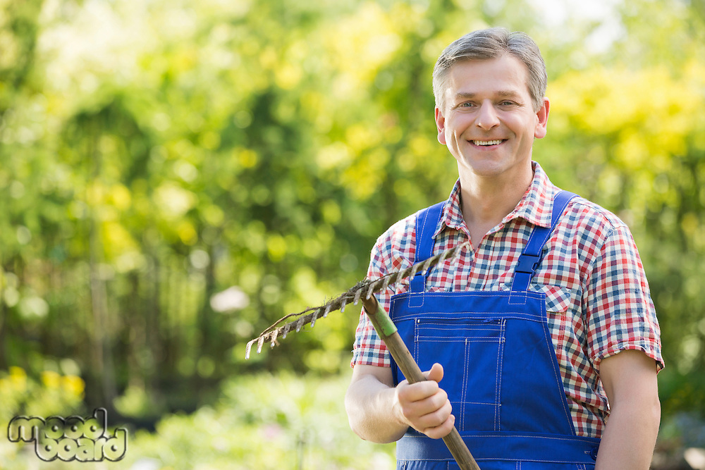 Portrait of smiling gardener holding rake in plant nursery
