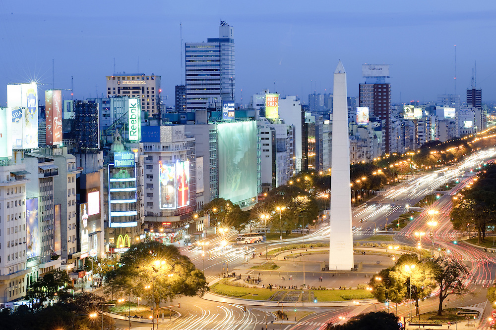 Buenos Aires, Argentina. Aerial view of 9 de Julio Avenue and the Obelisco monument, in Buenos Aires. The Obelisk of Buenos Aires (Obelisco de Buenos Aires) is a modern monument placed at the heart of the city, a venue for various cultural activities (usually sponsored by the city government) and other events. It is the traditional gathering spot for sports fans to celebrate when their favorite team wins, especially from the national football team, often resulting in colorful events that attract media coverage. It was also used by several acrobatic troupes to perform high-wire acts. Avenida 9 de Julio is the largest avenue in Buenos Aires, Argentina. Its name honors Argentina's Independence Day. (July 9, 1816) The avenue runs roughly one kilometer to the west of the Rio de la Plata waterfront, from the Retiro district in the north to Constitucion station in the south. The avenue has seven lanes in each direction.