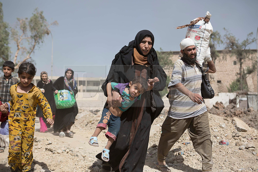 © Licensed to London News Pictures. 15/06/2017. Mosul, Iraq. Mosul residents cross the last stretch of open ground watched by Islamic State snipers to Iraqi Army positions after escaping from ISIS held territory in West Mosul today (15/06/2017).<br /> <br /> Despite heavy fighting between the Islamic State and Iraqi Security Forces many civilians have started to leave ISIS territory in West Mosul. Mosul residents, many of whom have been in hiding in their homes since the start of the West Mosul Offensive, often have to run through ISIS sniper and machine gun fire to reach the safety of Iraqi Security Forces positions. Photo credit: Matt Cetti-Roberts/LNP
