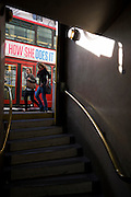 "Two young women walk past the entrance of London's Bank underground station whose steps go downwards from street level. As they pass the exit, a bus also drives through the gap of what we see on the road. The words 'How She Does It' refers to the Hollywood film titled ""I Don't Know How She Does It"" adapted from Allison Pearson's 2002 novel about a woman who ""has it all"". The steps of the underground station come downwards towards us with brass polished rails. Bank station, named after the Bank of England, opened in 1900 and is served by the Central, Northern and Waterloo and City lines, and the Docklands Light Railway."