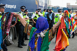London, UK. 6 September, 2019. An activist dances past Metropolitan Police officers monitoring a truck making a delivery to ExCel London beneath which an activist is locked in protest against DSEI, the world's largest arms fair. The road remained blocked for several hours. The fifth day of protests was themed as Stop The Arms Fair: Stop Climate Change in order to highlight links between the fossil fuel and arms industries.