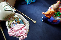 An infant sleeps in a cradle while as another child plays in the living room of one of the Children's Village homes Monday in Coeur d'Alene. The facility is seeing an increase in children dropped off to their crisis nursery which is putting increased financial pressure on the nonprofit.