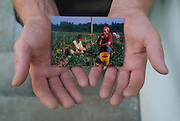 Many people from Prundul Bargaului, a small village in Romania, have gone abroad in search of work. This photo was taken in the village and shows one of the people in my project holding a photo taken in Germany.