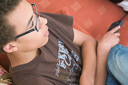 Portrait of a teenage boy watching television,
