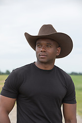 Portrait of a good looking African American cowboy with green eyes