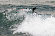 A sea kayaker breaks through waves while paddling on a rough Lake Superior near Marquette Michigan.
