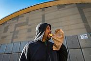 Philadelphia, Pennsylvania / USA. Steve from Bucks County enjoys a donut infront of the abandoned market on Frankford Ave.  April 26 2018. Credit: Chris Baker Evens.