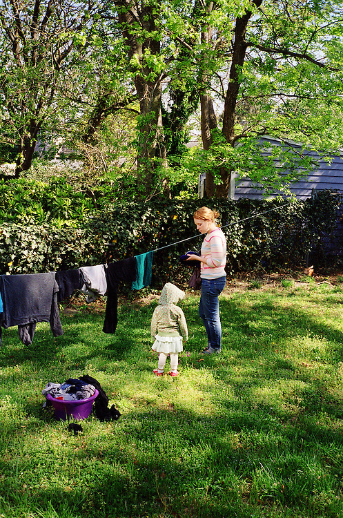 Melissa Eich, 22, and her daughter Madelyn Avery Eich, 2, hang laundry on the clothesline in their back yard in Norfolk, Virginia on Sunday, April 18, 2010.