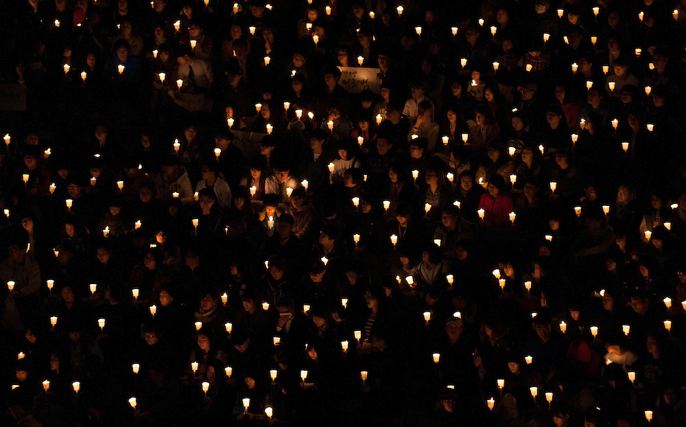 People hold candles during a vigil in Ansan, Gyeonggi Province. Students, parents, teachers, and others from the community gathered at a park near Danwon High School to pray for the missing and mourn the dead from the Sewol ferry sinking. The ship sank on April 16, 2014, off the southwest coast of Korea, carrying more than 400 passengers, most of them Danwon High School students on a school trip to Jeju Island. 174 people were saved, and rescuers have been searching for other survivors for days, but hundreds of people are still listed as missing. The sinking is being called South Korea's worst maritime disaster in decades.