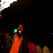A football fan waves  a flaming aerosol can aloft as crowds revelled in the street in Accra, Ghana to celebrate Ghana's progression to the next round of the FIFA World Cup despite their 1 - 0 loss to Germany. 23 June 2010.