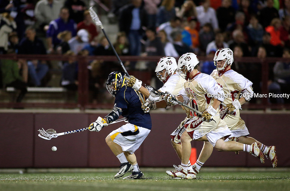 SHOT 4/5/13 7:26:38 PM - Marquette's Tyler Gilligan #17 goes after a loose ball while being chased by a trio of University of Denver defenders during their NCAA Men's Lacrosse game at the Peter Barton Lacrosse Stadium on the University of Denver's campus. The University of Denver won the game 15-4.(Photo by Marc Piscotty / © 2013)