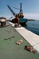 Un operaio sulla banchina del porto di Brindisi, si prepara per sistemare una grossa catena che servirà a far attraccare le barche a vela.