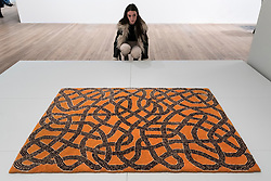 "© Licensed to London News Pictures. 09/10/2018. LONDON, UK. A visitor views ""Rug"", 1959, executed by Gloria Finn Dale.  Preview of the UK's first exhibition of works by German artist Anni Albers at Tate Modern who used the ancient art of hand-weaving to produce works of modern art.  Over 350 of her artworks from major collections from Europe and the US are on show 11 October to 27 January 2019.  Photo credit: Stephen Chung/LNP"