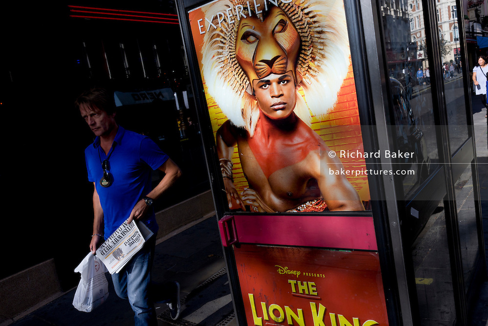 An ad poster with the actor Andile Gumbi as Simba in the Lion King is on the door of a central London telephone kiosk for the Disney production. The man in blue walking past is wearing his taxi driver's license badge around his neck and has perhaps taken a break from his job driving around the capital to pick up an Evening Standard newspaper and some sandwiches from the Pret a Manger food chain. The Lion King, the musical of the Disney cartoon has been running in London's West End since October 1999, breaking its own box office record, taking more than £34m during 2010 - £2m more than the previous year - and ending the year with its best ever week of ticket sales. Big musicals are so far defying the economic gloom, and theatre in general is proving surprisingly resilient. More than 800,000 saw this Disney musical cartoon in its 11th year in West End