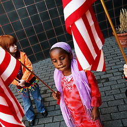 Kyle Green | The Roanoke Times<br /> April 20, 2007 (left to right), Virginia Heights Elementary kindergarden students, Amber Albert (age 5), Kumo Abdi (age 5), and Maya Ingram (age 5) hold flags during a day of mourning ceremony held at the school in Roanoke, Virginia. Friday was declared a day of mourning by Governor Tim Kaine in honor of the 32 Virginia Tech students who were killed by a lone gunman on Monday.