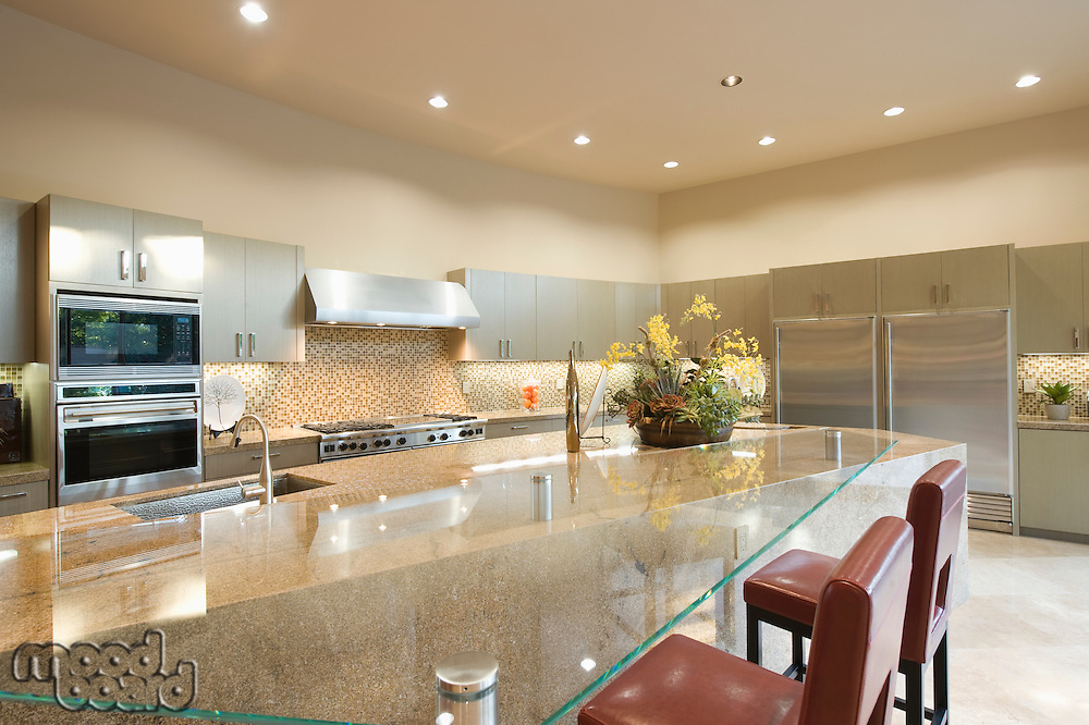 Glass topped kitchen surface with stainless steel fitted units