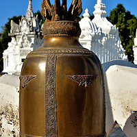 Bronze Temple Bell at Wat Suan Dok in Chiang Mai, Thailand <br /> This bronze, lotus-shaped temple bell is the largest of several around the perimeter of the Chet Ton Dynasty royal mausoleums at Wat Suan Dok. Called a bonshō, they are often seen at Buddhist temples in Thailand.  They do not have a clapper but instead are rung with a mallet and in some cases are used to summon monks.