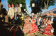 "Each day of the Seville Feria d'Abril, the fiesta begins with the parade of carriages and riders, at midday, carrying Seville's citizens to the bullring, la Real Maestranza...The Feria de abril de Sevilla, ""Seville April Fair"" dates back to 1847. During the 1920s, the feria reached its peak and became the spectacle that it is today. It is held in the Andalusian capital of Seville in Spain. The fair generally begins two weeks after the Semana Santa, Easter Holy Week. The fair officially begins at midnight on Monday, and runs six days, ending on the following Sunday...For the duration of the fair, the fairgrounds and a vast area on the far bank of the Guadalquivir River are covered in rows of casetas (individual decorated marquee tents which are temporarily built on the fairground). Some of these casetas belong to the prominent families of Seville, some to groups of friends, clubs, trade associations or political parties. From around nine at night until six or seven the following morning, at first in the streets and later only within each caseta, crowds of people party and dance Sevillanas, traditional Flamenco dances, Sevillan style drinking Jerez sherry, or Manzanilla wine, and eating tapas. Men and women dress up in their finery, the traditional ""traje corto"" (short jacket, tight trousers and boots) for men and the ""faralaes"" or ""trajes de flamenca"" (flamenco style dress) for women. The men traditionally wear hats called ""cordobés""."