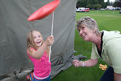 Grandmother encouraging girl with her plate spinning skills at a Parklife summer activities event,