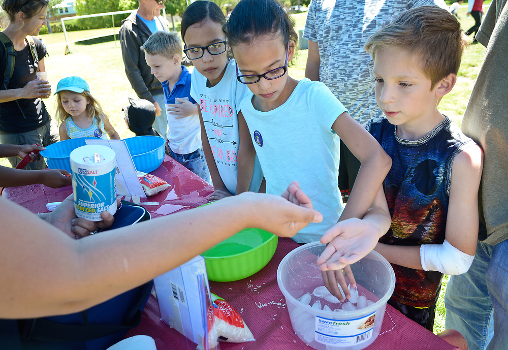 mkb052017l/metro/Marla Brose --  Gabriel Baca, 8, right, and his sister Briana Baca, second from right, test how sticky salty ice becomes during a demonstration at the Launch to Learn table at the Tiguex Park, Saturday, May 20, 2017. Launch to Learn 2017 is a summer science program that works to curb summer learning loss. For more information about  the program's Family Summer Adventure Guide, visit  www.launchtolearn.org.  (Marla Brose/Albuquerque Journal)