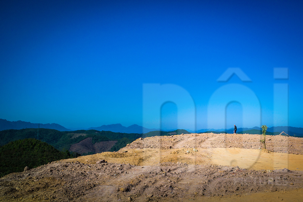 A figure stands on a muddy hilltop beside Road 13 between Pak Mong and Oudom Xai (Muang Xay), Oudomxay Province, Laos, Southeast Asia