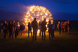 © licensed to London News Pictures. Wiltshire, UK 10/07/2012. People watching a fire sculpture at Stonehenge as they enjoy Fire Garden event which is part of the London 2012 Festival and Salisbury International Arts Festival. The heritage site surrounded with fire sculptures and fire posts by French outdoor fire alchemists Compagnie Carabosee. Photo credit: Tolga Akmen/LNP