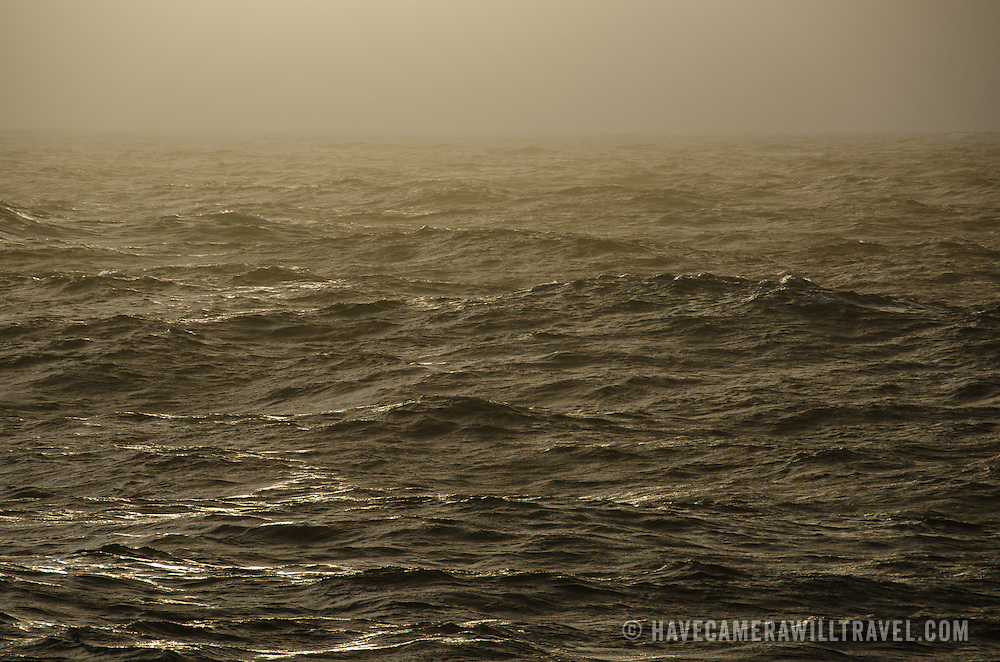 A passing rain squall captures the dusk light on relatively calm waters of Drake Passage in the Southern Ocean between South America and Antarctica.