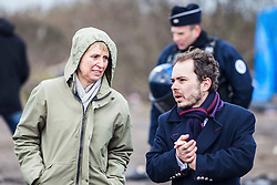 © Licensed to London News Pictures. Calais, France. 02/03/16. With a police escort, Calais Prefect Fabienne Buccio (left) surveys progress made on the third day of the demolition of the Calais 'Jungle' camp. French authorities have begun clearing the southern half of the camp, which charities estimate to contain some 3,500 people. Photo credit: Rob Pinney/LNP