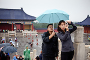 "Man holding an umbrella for his wife during she is   photographing at ""The Temple of Heaven"" which is a complex of Taoist buildings situated in the southeastern part of central Beijing. Beijing is the capital of the People's Republic of China and one of the most populous cities in the world with a population of 19,612,368 as of 2010."