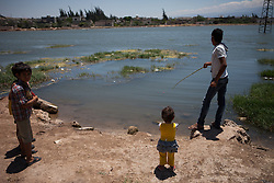 Syria.<br /> A syrian resident of Al-Qala tries to fish with a small stick in a small lake in the town of Al-Qala a small town with an ancient castle occupied by the Syrian regime in Hama province, Syria,<br /> 15th June 2013<br /> Picture by Daniel Leal-Olivas / i-Images