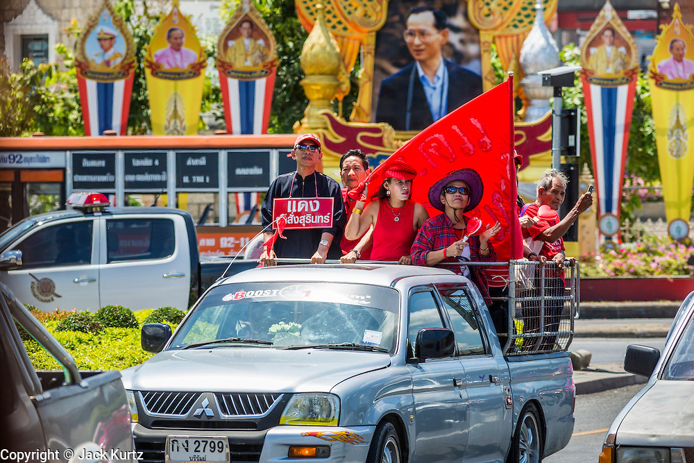 08 MAY 2013 - BANGKOK, THAILAND: A motorcade of Thai Red Shirts passes a portrait Bhumibol Adulyadej, the King of Thailand, on their way to the Thai parliament building. A splinter group of the Red Shirts, Thai supporters of exiled Prime Minister Thaksin Shinawatra, have besieged the Thai Constitutional Court for the last three weeks calling for the resignation of the justices, who have indicated they might oppose a proposed constitutional reform which would grant amnesty to people convicted of political crimes since 2007. This would probably include Thaksin. The justices have refused to step down. Wednesday the protesters moved their protest to the Thai Parliament, which is largely powerless to intervene.   PHOTO BY JACK KURTZ