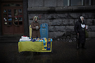 European and Ukrainian souvenirs vendor stands next to a begging woman near Independence Square on December 17, 2013 in Kiev, Ukraine. Thousands of people have been protesting against the government since a decision by Ukrainian president Viktor Yanukovych to suspend a trade and partnership agreement with the European Union in favor of incentives from Russia was made recently.