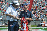 Retiring Associate Athletic Director for Media Relations Langston Rogers (center), is congratulated by head coach Houston Nutt (left) and athletic director Pete Boone during halftime presentations in Mississippi's Grove Bowl in Oxford, Miss. on Saturday, April 17, 2010.