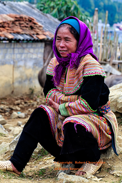A woman huddled against the cold proudly displays her colourful traditional dress of the Flower Hmong tribe, at the morning market, Bac Ha Vietnam.