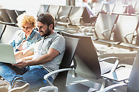 Portrait of man showing funny picture with his wife while waiting in airport