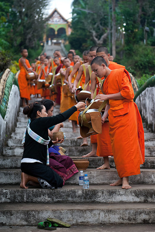 Novices and monks collecting alms in Hua Xai, Laos.