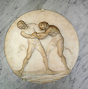 Lutteurs. Stone relief of two wrestlers in each others grips, struggling to overcome their opponent.