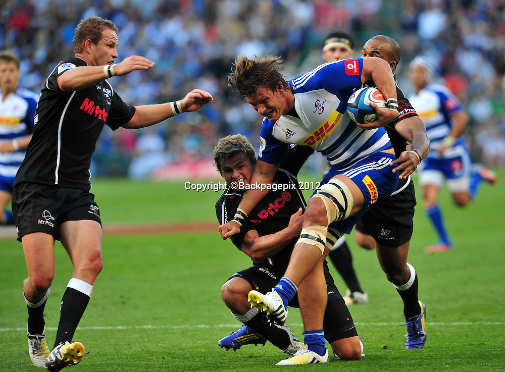 Michael Rhodes of the Stormers is tackled by Pat Lambie and JP Pietersen of the Sharks during the Stormers 2013 Super Rugby game between the Stormers and the Sharks at Newlands Rugby Stadium on 13 April 2013 ©Ryan Wilkisky/BackpagePix